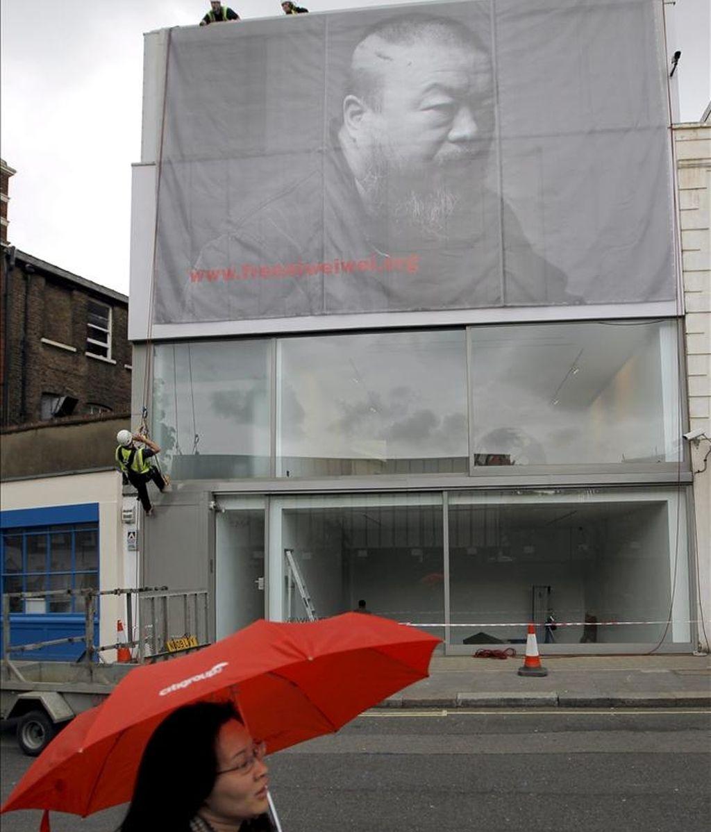 Unos trabajadores despliegan un gran cartel con un retrato en blanco y negro del artista chino Ai Weiwei antes de la inauguración de una exposición retrospectiva sobre los últimos seis años de su obra en la galería Lisson en Londres, Reino Unido. EFE
