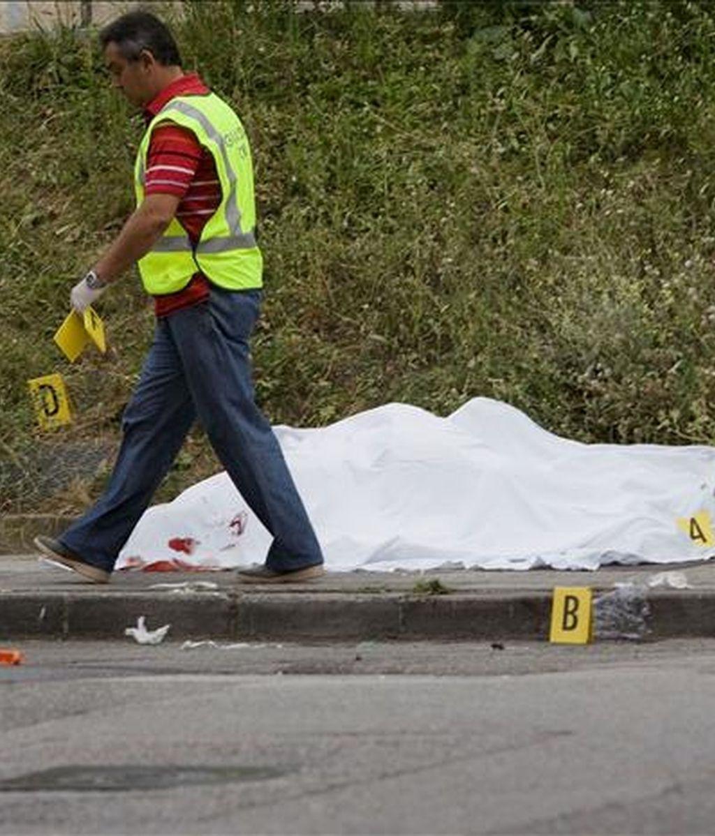 Un agente de la Guardia Civil junto al cuerpo de uno de los dos fallecidos en un tiroteo en las proximidades del polideportivo de Ujo, un pueblo del municipio asturiano de Mieres. EFE