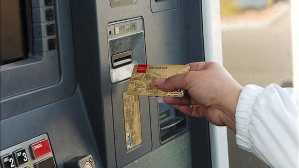 Una mujer saca dinero de un cajero automático. EFE/Archivo