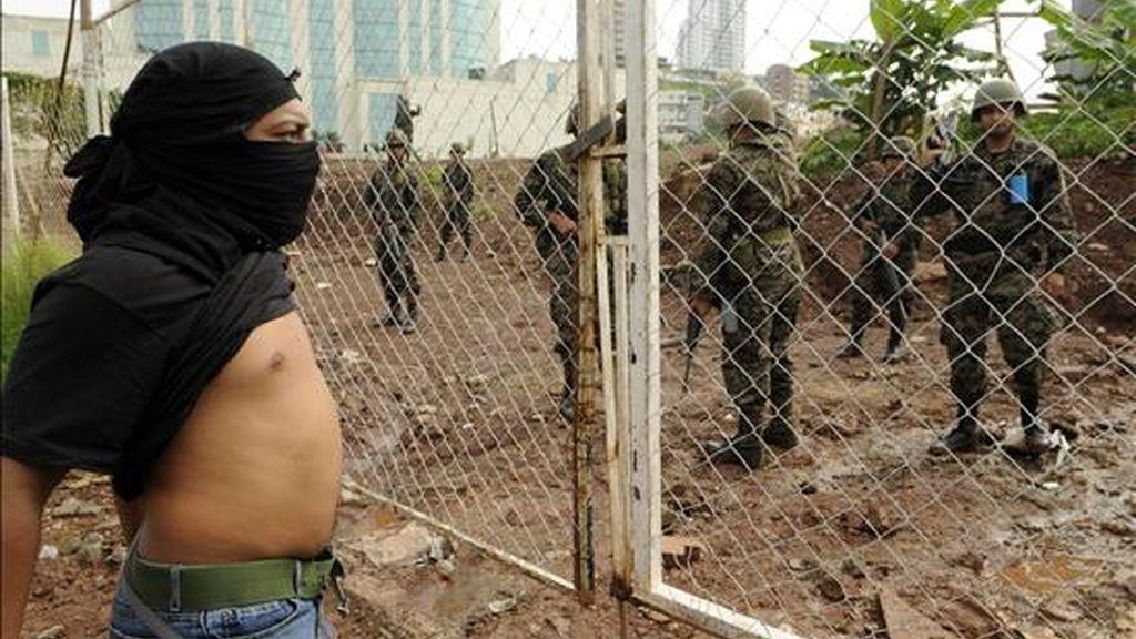Manifestantes encapuchados se concentran frente a la Casa Presidencial, en Tegucigalpa (Honduras), ante la vigilancia de miembros del ejército. EFE