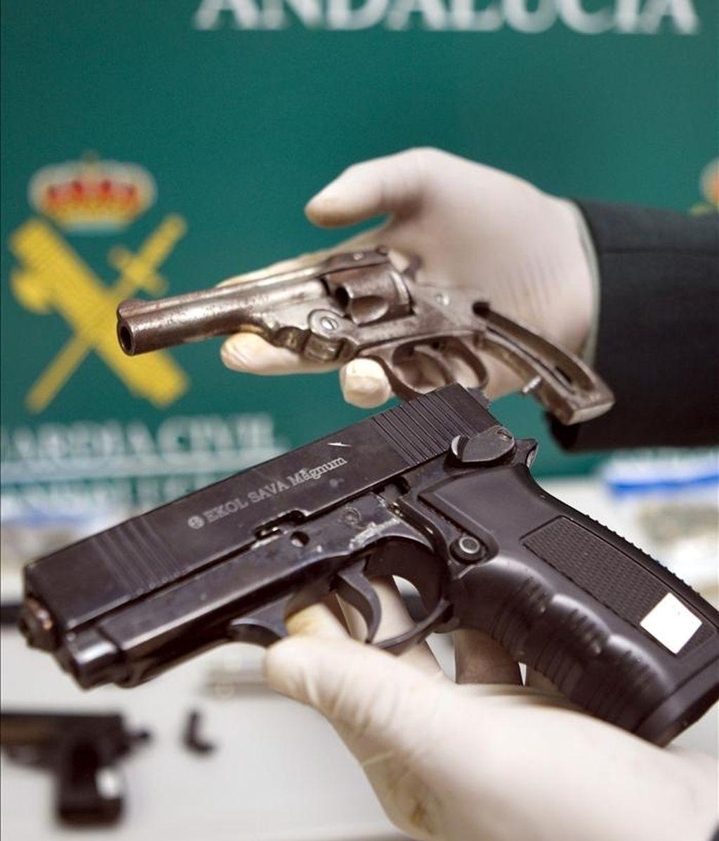 Un miembro de la Guardia Civil meustraa dos de las armas incautadas en Sevilla a cuatro personas que formaban una red dedicada a transformar armas de fuego en reales, según informó hoy el portavoz del Instituto Armado. EFE