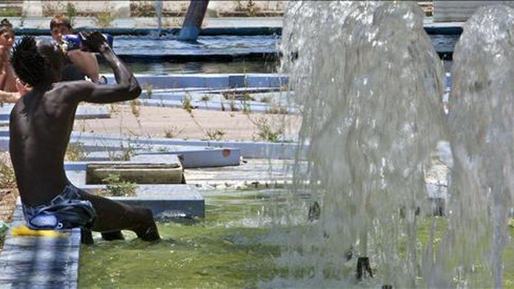Una persona se refresca en una fuente céntrica de Sevilla. EFE