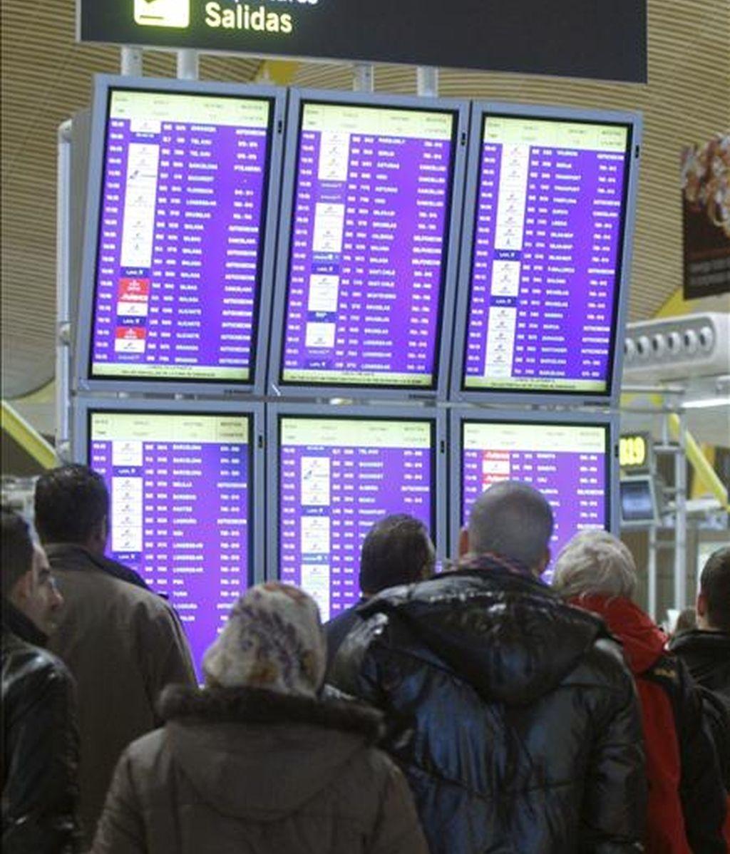En la imagen, numerosos pasajeros esperan en el aeropuerto de Barajas la salida de sus aviones. EFE/Archivo