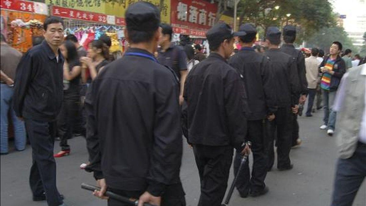 Un año después de la revuelta étnica entre uiuges y chinos que ocasionó casi 200 muertos, la capital de la región autónoma de Xinjiang, Urumqi, amaneció hoy en tensión y bajo la vigilancia del Ejército chino para evitar nuevos conflictos. En la foto, Guardias de seguridad patrullan por las calles del Mercado Nocturno de Urumqi. EFE