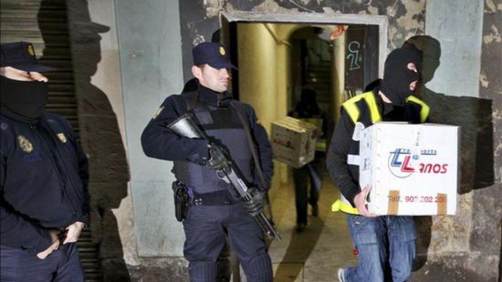 Miembros de la Policia Nacional retiran varias cajas con documentación tras el registro de una vivienda en la calle Carretas de Barcelona durante la operación antiterrorista que se llevó a cabo en el barrio del Raval el pasado 3 de febrero. EFE