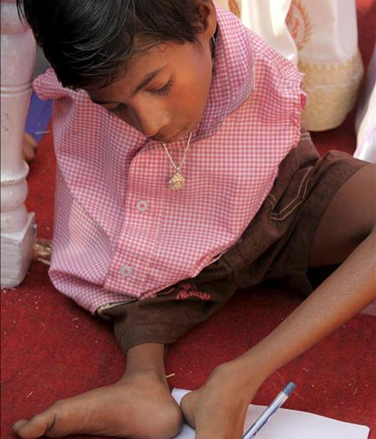 Jagannath Gharai, un menor discapacitado de 10 años, sostiene un bolígrafo con una de sus extremidades durante la celebración del Día Internacional de las Personas con Discapacidad en Calcuta, India, hoy, 3 de diciembre de 2010. EFE
