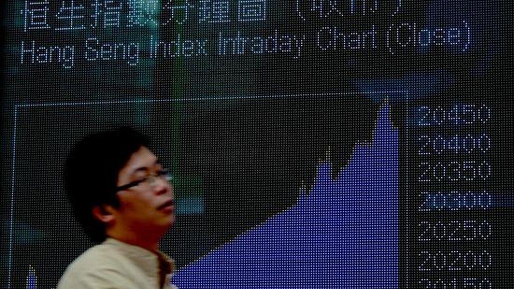 Un hombre pasa delante de un panel electrónico en la Bolsa de Hong Kong, China. EFE/Archivo