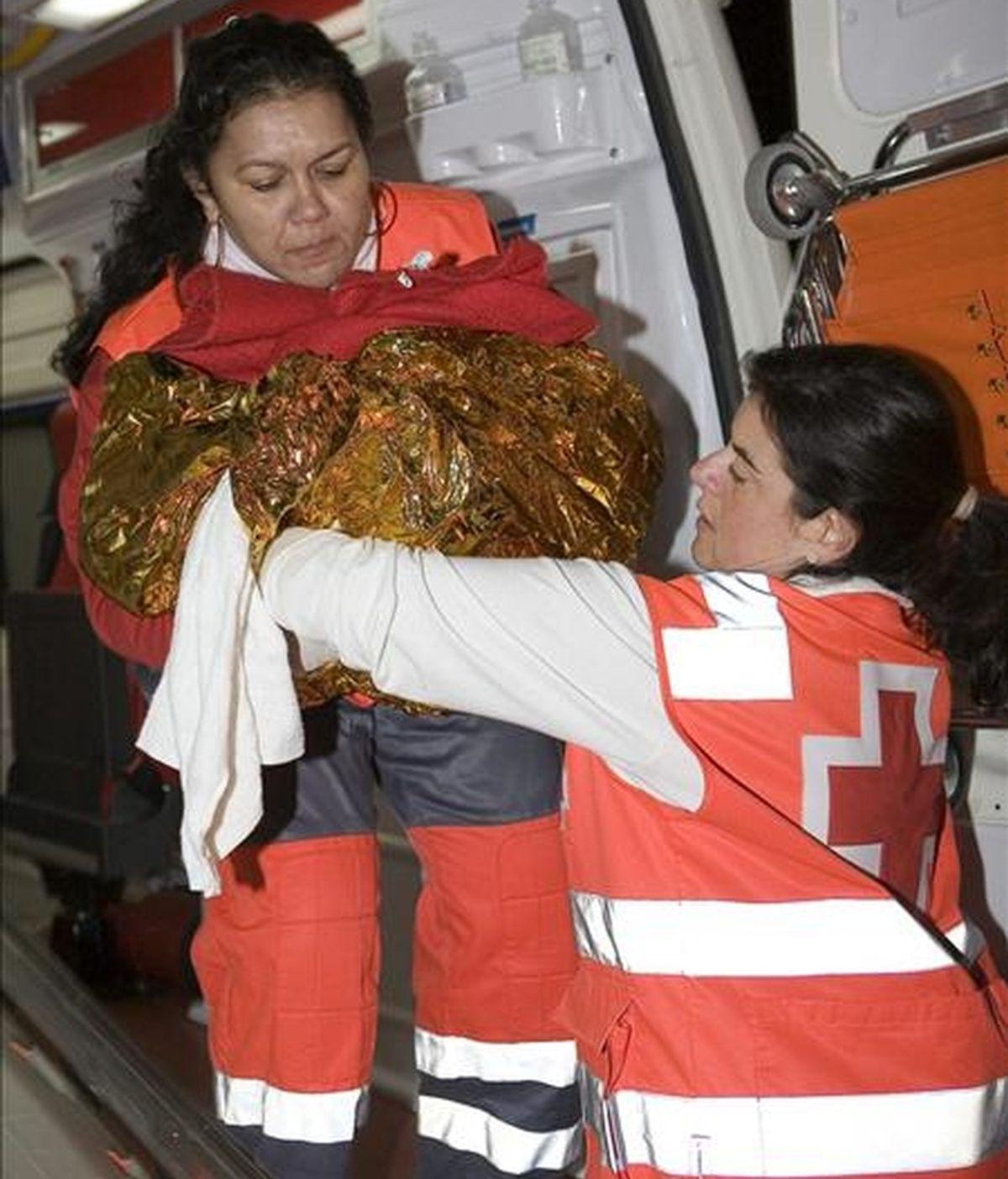 Dos miembros de la Cruz Roja sostienen entre mantas térmicas al bebé que nació en la patera quefue interceptada, esta tarde, por miembros del Servicio Marítimo de la Guardia Civil y de Salvamento Marítimo en las cercanías de la Isla de Alborán. EFE