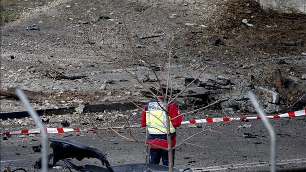 Un agente de policía observa el lugar donde esta mañana hizo explosión un coche bomba en el Campo de las Naciones de Madrid. EFE