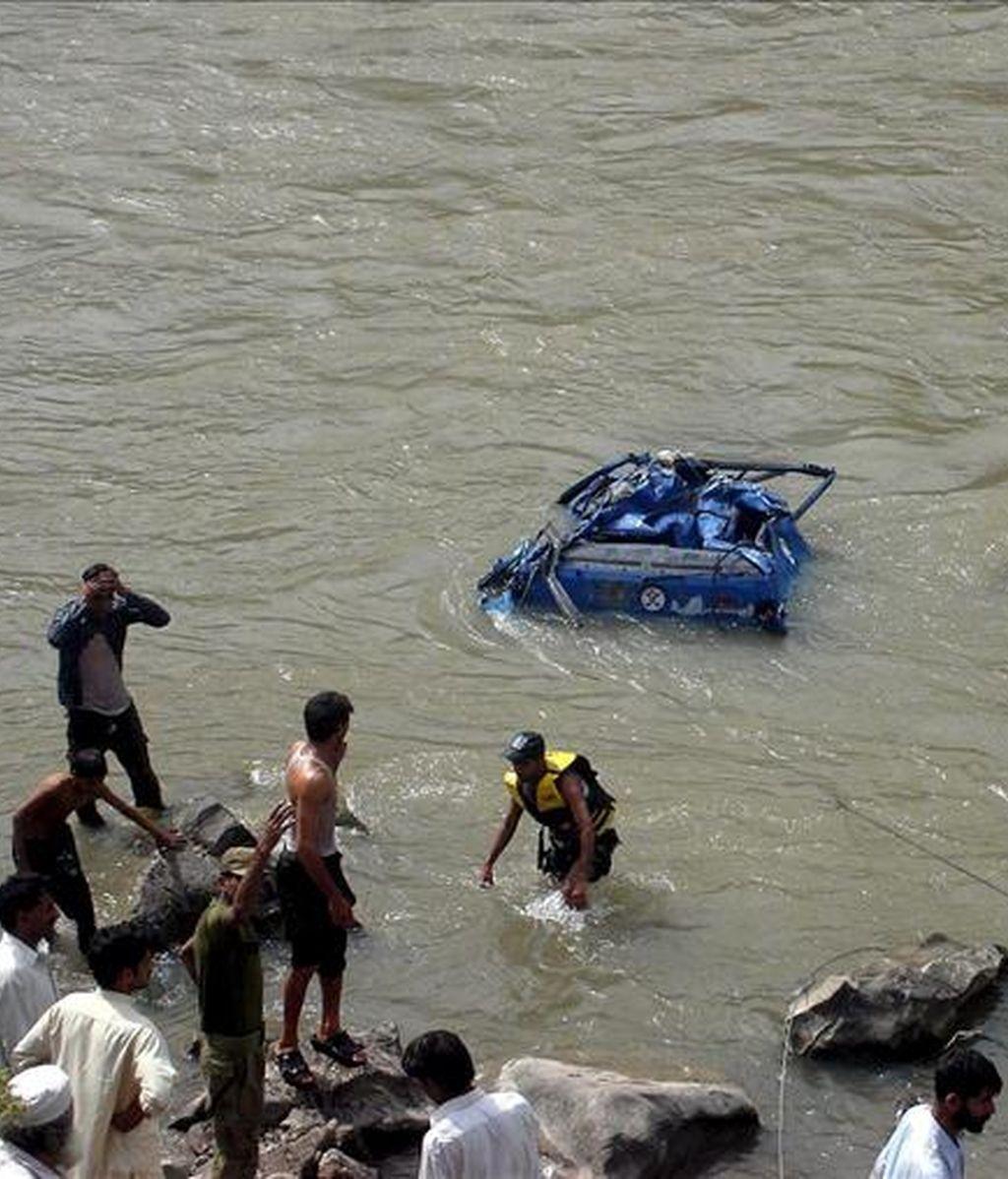 Rescatistas buscan los restos de un autobus escolar que se precipitó por un barranco cerca de Muzaffarabad, la capital de la parte paquistaní de Cachemira. EFE