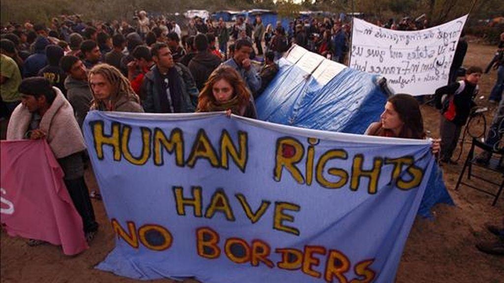 """Inmigrantes portan una pancarta con el mensaje """"los derechos humanos no tienen fronteras"""", horas antes de la operación de desmantelamiento de un campamento de inmigrantes indocumentados en los alrededores del puerto de Calais (noroeste de Francia). EFE/Archivo"""