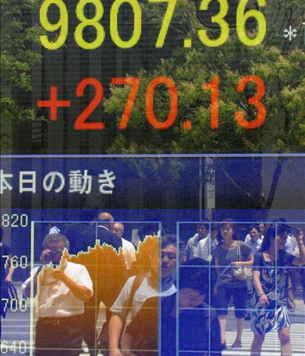 Peatones reflejados en un escaparate con una pantalla con el cierre de la Bolsa de Tokio. EFE/Archivo