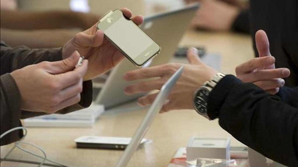 Un cliente atiende a las observaciones de un vendedor en una tiena de móviles. EFE/Archivo