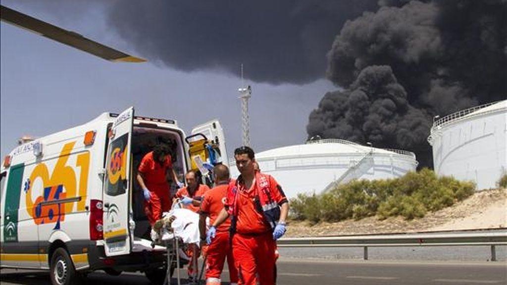 Miembros del 061 evacúan a uno de los operarios que resultaron heridos de diversa consideración en un incendio registrado ayer  en la Refinería La Rábida de CEPSA en Palos de la Frontera (Huelva). EFE