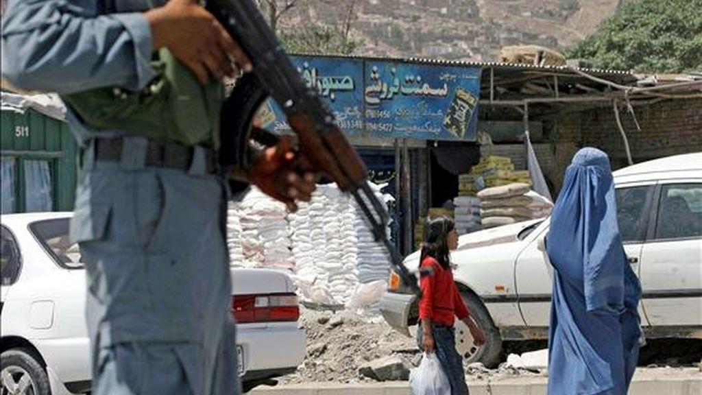 Un policía afgano vigila cerca del puesto de control montado en una carretera hoy, lunes 19 de julio de 2010 en Kabul (Afganistán) un día antes de la conferencia internacional de donantes de Kabul. Delegados de más de 70 países y organizaciones participarán en la cumbre. EFE