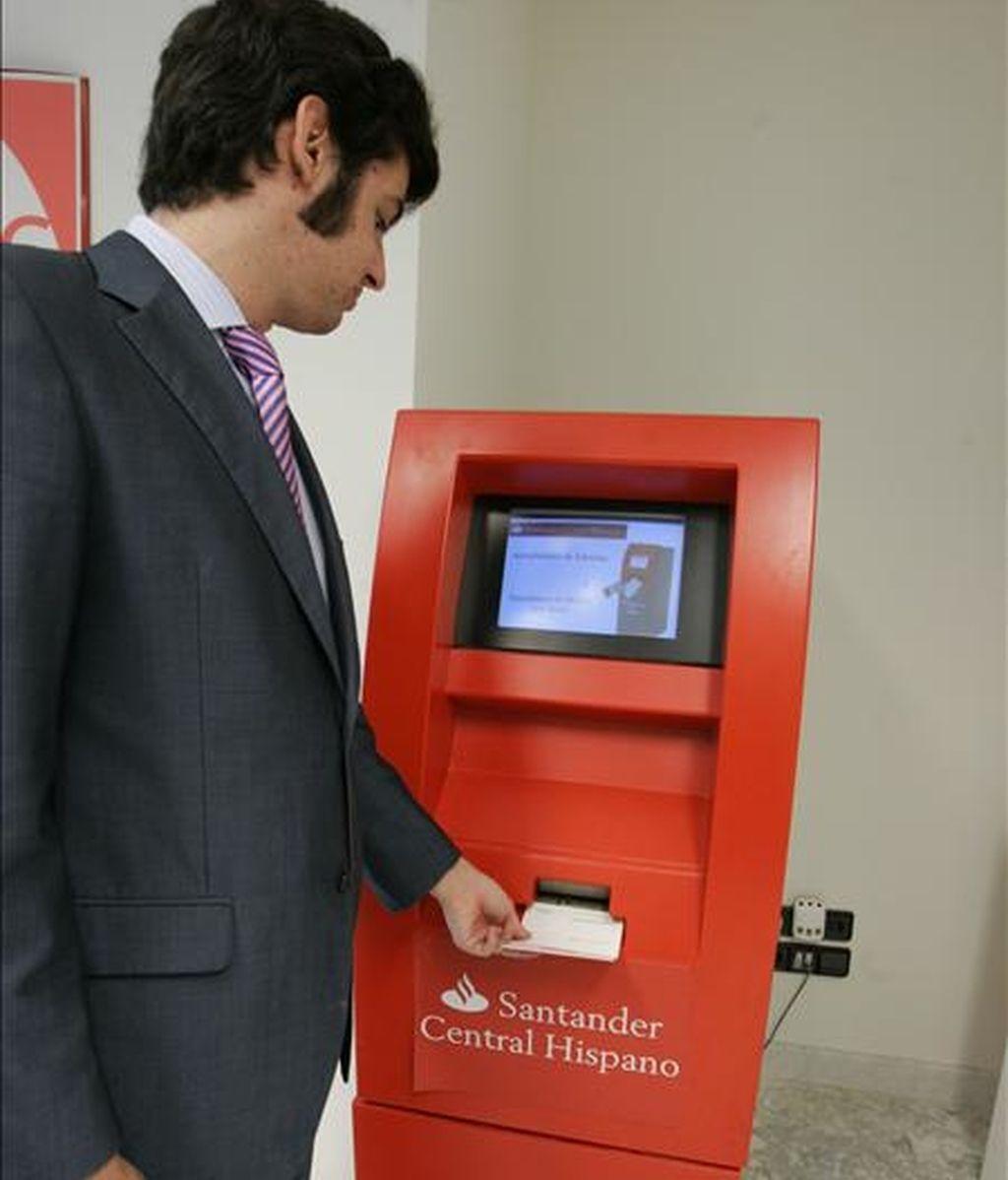 Un cliente actualiza su libreta en un cajero automático de una oficina del Banco Santander. EFE/Archivo
