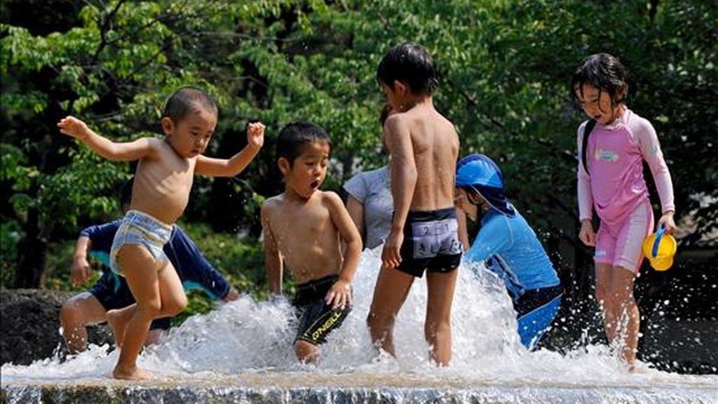 Un grupo de niños juega con el agua en una fuente en el centro de Tokio (Japón). EFE/Archivo