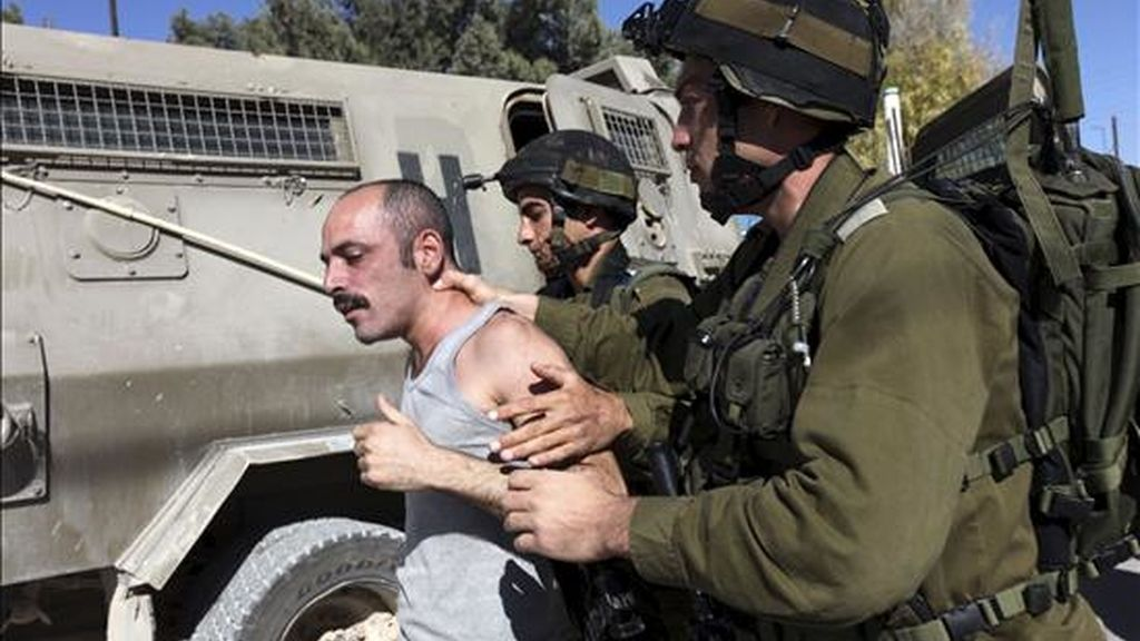 Soldados israelíes detienen a un manifestante palestino durante una protesta contra el muro de separación israelí, en la población de Maasarah, cerca de Belén (Cisjordania). EFE/Archivo
