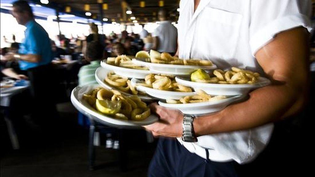 Un camarero porta varios platos en un chiringuito de Málaga. EFE/Archivo