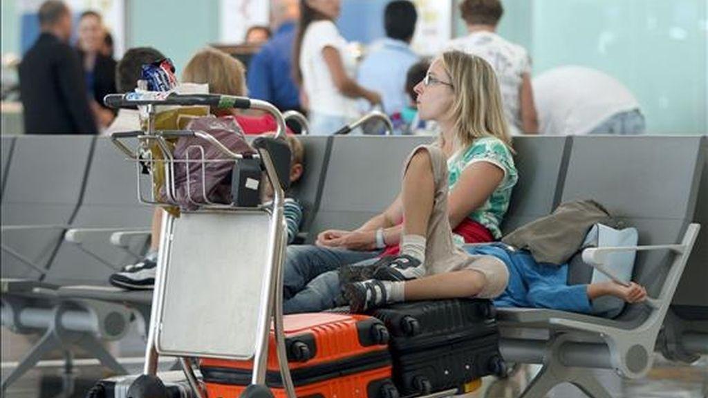 Una familia espera en la Terminal 1 del aeropuerto de El Prat (Barcelona). EFE/Archivo