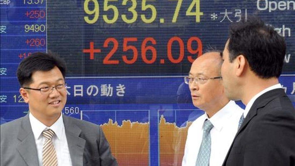 Tres hombres de negocios japoneses conversan ante una pantalla en la que aparece el índice Nikkei, en el centro de Tokio (Japón). EFE/Archivo