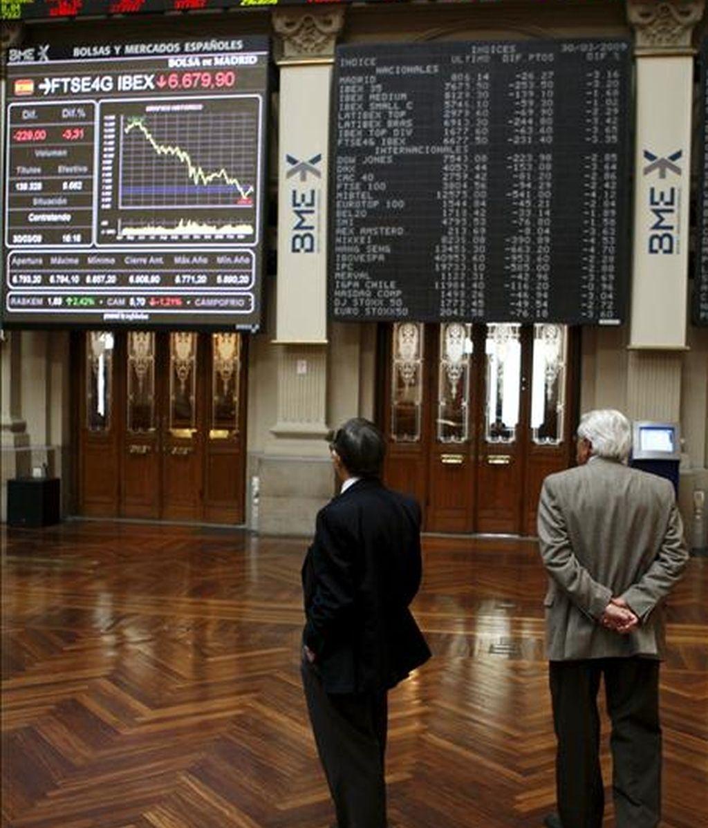 Dos inversores observan el panel de cotizaciones del Ibex-35 en la Bolsa de Madrid. EFE/Archivo