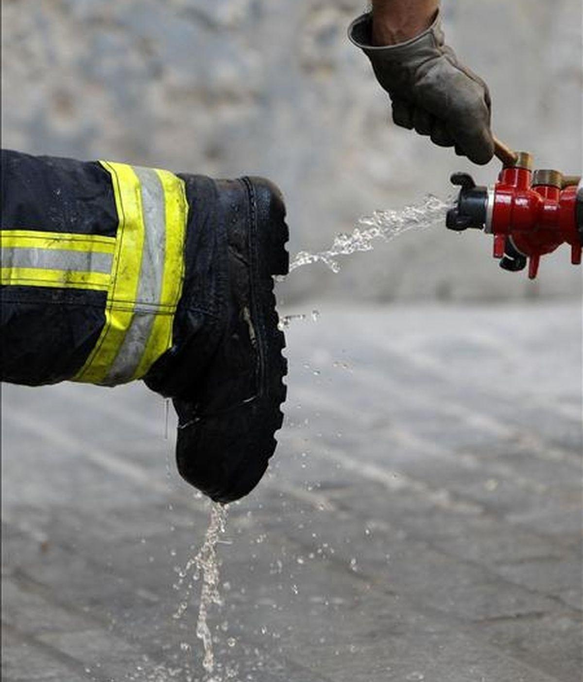 Un bombero limpia sus botas tras declarar extinguido un incendio. EFE/Archivo
