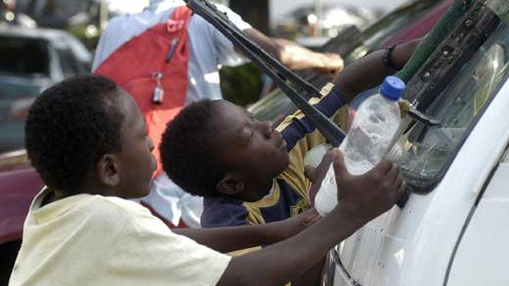 Dos niños colombianos trabajan limpiando los parabrisas de algunos vehículos que se detienen en los semáforos. Foto: EFE