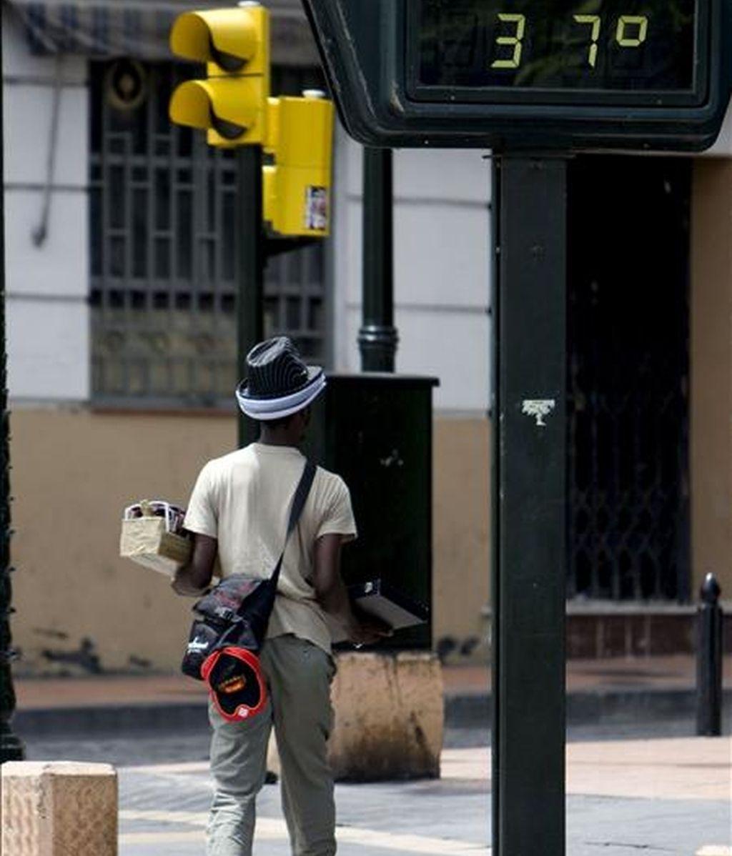 Un vendedor ambulante pasea bajo un termómetro en el casco histórico de Zaragoza. EFE
