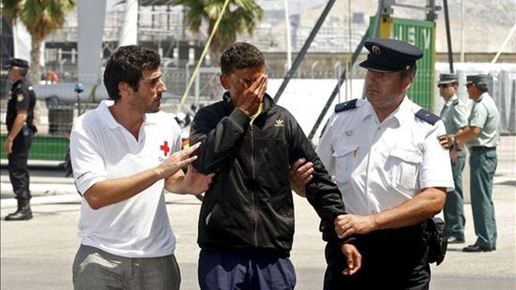 Una de las once personas que han sido interceptadas hoy en una patera a unas 40 millas mar adentro a la altura de Benidorm (Alicante) es atendido por voluntarios de Cruz Roja y de la Policía Nacional a su llegada al Puerto de Alicante. EFE