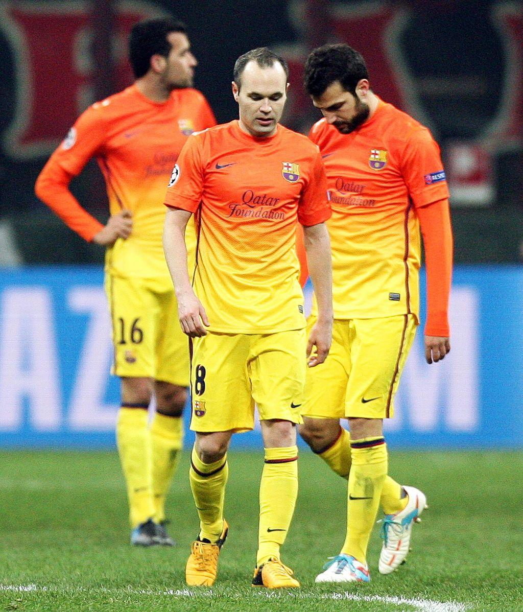 Los centrocampistas del FC Barcelona, Andres Iniesta y Cesc Fábregas (dcha), se lamentan tras recibir un gol del AC Milan, durante el partido de ida de los octavos de final de la Liga de Campeones disputado en el estadio Giuseppe Meazza de Milán