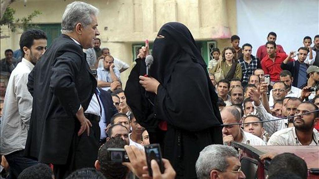 Una mujer muestra su dedo índice marcado con tinta como prueba de haber ejercido su derecho al voto al candidato Hamdine Sbbah (2ºizda) quien decidió retirar su candidatura después de supuestas irregularidades en las elecciones al Parlamento, en Kafr el-Sheikh (Egipto) ayer, 28 de noviembre de 2010. EFE