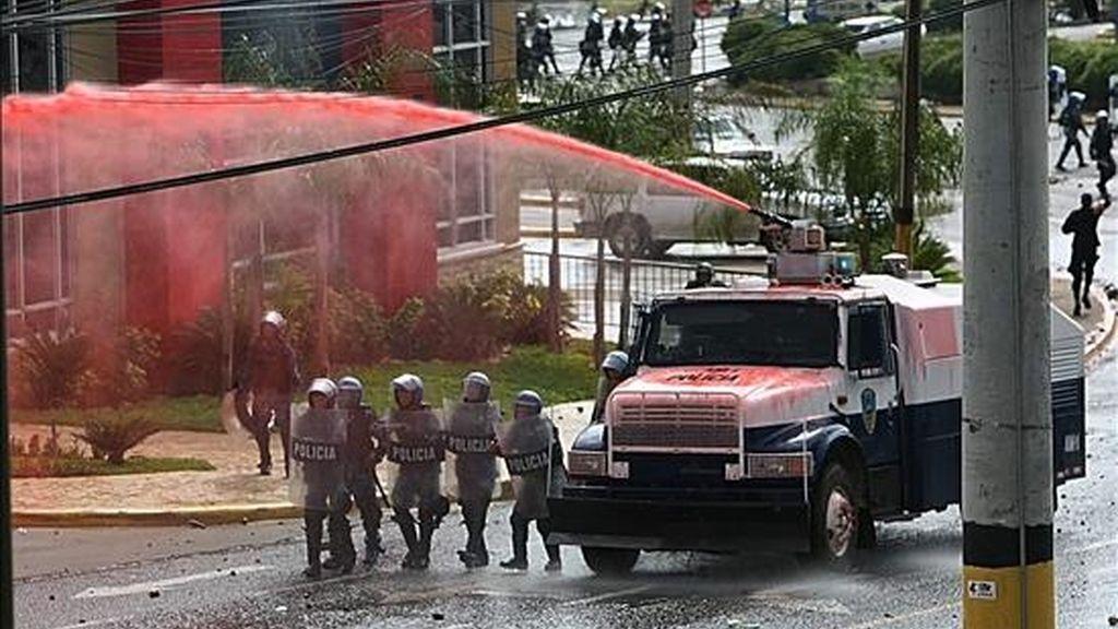 Imagen de las fuerzas policiales que, con el apoyo de gases lacrimógenos, vehículos blindados y dos helicópteros, desalojan a varios piquetes de simpatizantes del depuesto presidente Manuel Zelaya. EFE