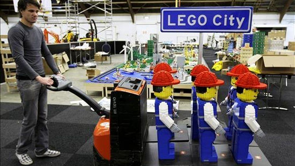 """Un operario empuja un carrito de figuras de obreros hechas con bloques de plástico interconectables en la exposición """"Lego World"""" en Zwolle (Holanda). EFE/Archivo"""