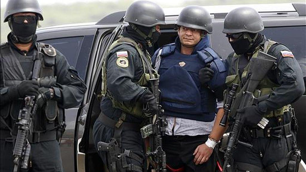 El salvadoreño Francisco Chávez Abarca (c), solicitado por Interpol por delitos de terrorismo es custodiado en el aeropuerto caraqueño de Maiquetía (Venezuela), antes de abordar el avión para su traslado a Cuba. EFE