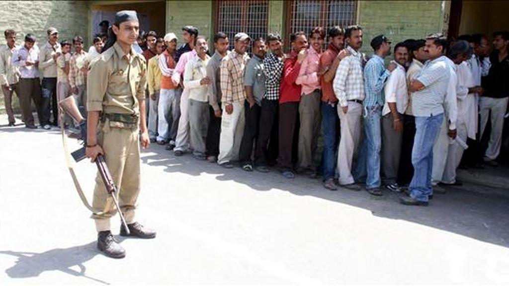 Un policía hace guardia en el extrior de un colegio electoral del pueblo indio de Suchit Garh. EFE