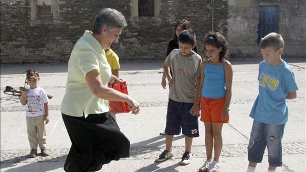 Una vecina enseña un grupo de niños a jugar al avión, uno de los juegos habituales en su infancia. EFE/Archivo