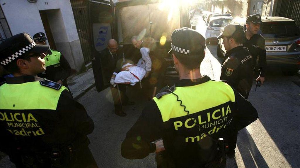 Agentes de la Policía Municipal observan como los empleados de los servicios funerarios introducen en el furgón el cadáver de la mujer de unos cuarenta años que falleció ayer degollada en su domicilio de la calle Ascensión Bielsa en el distrito madrileño de Puente de Vallecas.  EFE