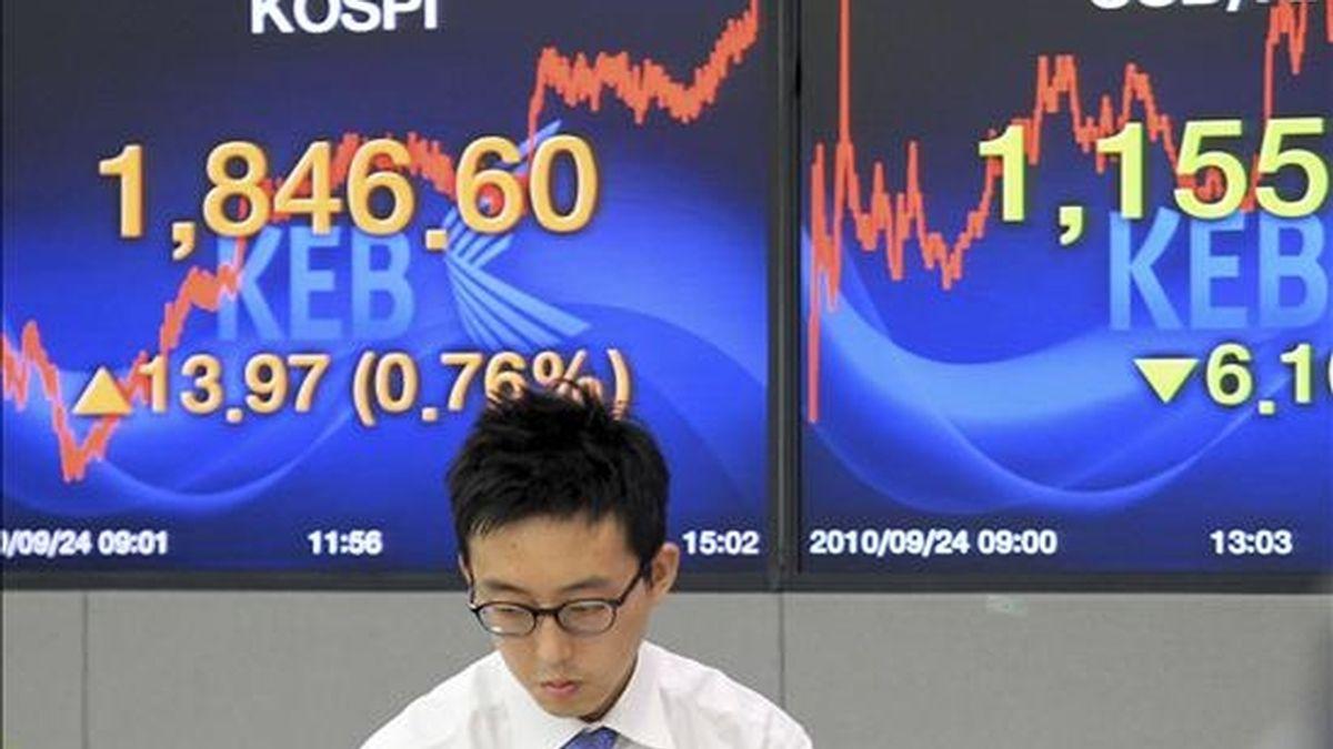 Un agente de bolsa trabaja en el parqué mientras las pantallas reflejan el índice Kospi del mercado surcoreano. EFE/Archivo