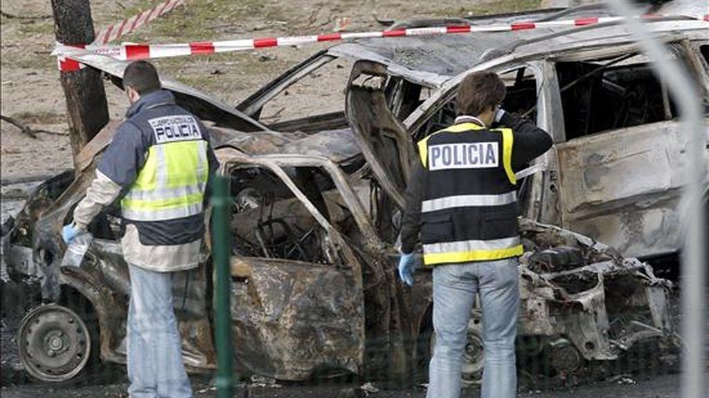 Dos agentes de policía observan los coches destrozados por la explosión de un coche bomba ocurrida esta mañana en el Campo de las Naciones de Madrid, en la que no ha habido víctimas. EFE