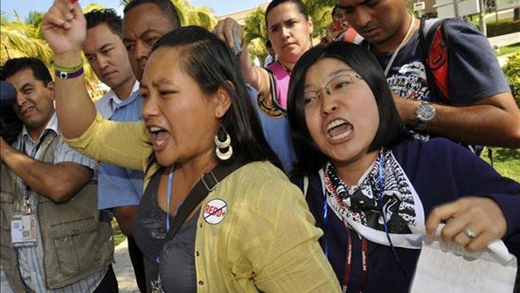 """Un grupo de jóvenes de la organización """"Soluciones de los pueblos para la justicia climática Norteamérica"""" gritan consignas este 7 de diciembre en el marco de la XVI Conferencia de las Partes de la ONU sobre Cambio Climático, en Cancún, México. EFE"""