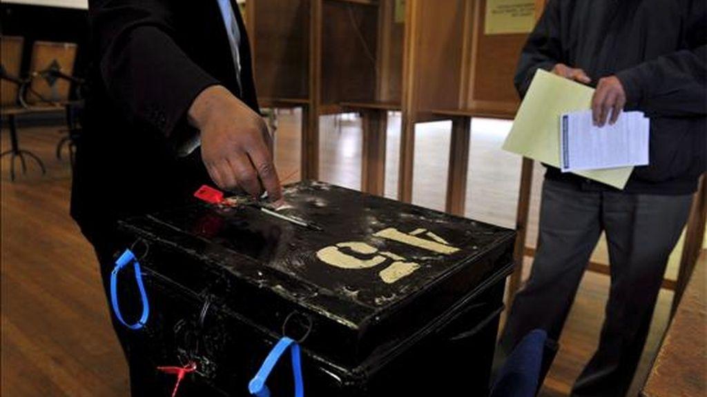 Un elector deposita su voto para las elecciones europeas y parciales inglesas en un colegio electoral en Putney, Londres Oeste (Reino Unido) hoy jueves 4 de junio. EFE