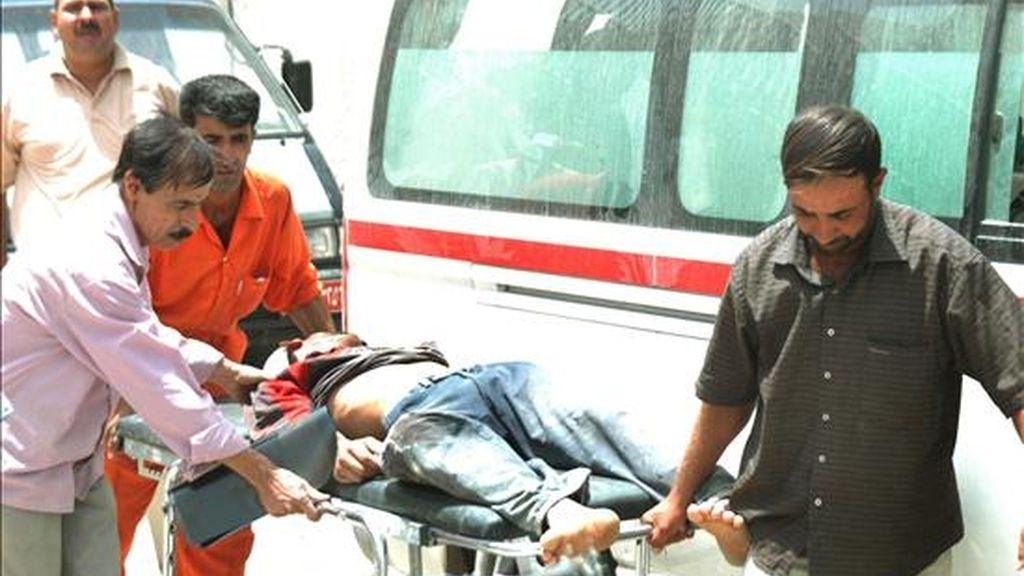 Varias personas trasladan el cuerpo sin vida de un hombre que murió tras un atentado en el distrito de Doura en Bagdad. EFE/Archivo