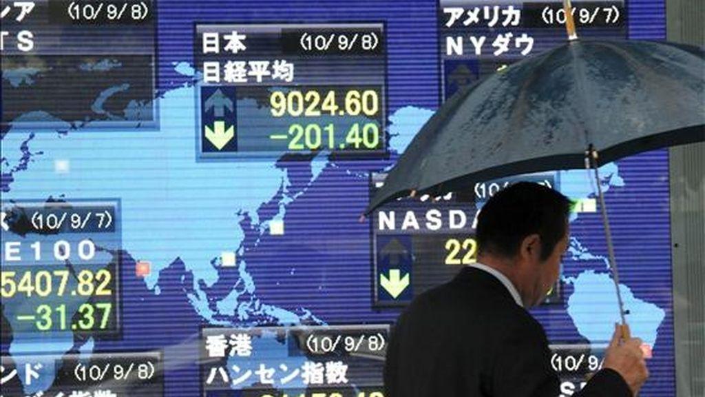 Un hombre pasa junto a una pantalla en la que se muestran los datos de los parqués internacionales, en Tokio (Japón). El índice Nikkei de la Bolsa de Valores de Tokio subió en su apertura un 0,67 por ciento. EFE