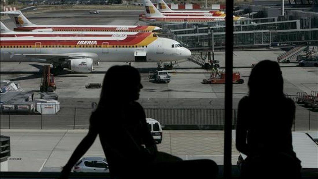Dos jóvenes conversan frente a varias aeronaves de Iberia en el aeropuerto de Madrid-Barajas. EFE/Archivo