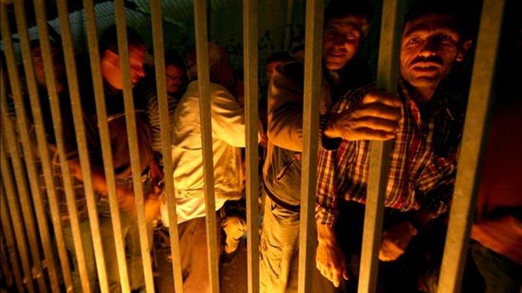 Un grupo de palestinos descansa mientras esperan a cruzar un puesto de control en Belén (Cisjordania) antes de cruzar a Israel, donde se encuentra su puesto de trabajo, hoy, 18 de junio. Según datos de Naciones Unidas, Israel tiene más de 630 puestos en Cisjordania, de los cuales, más de noventa están controlados por personal militar. EFE