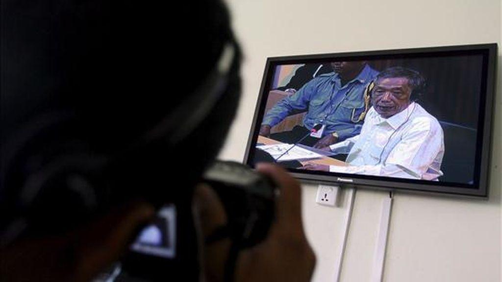 """Un fotógrafo camboyano toma imágenes del ex comandante del Jemer Rojo Kaing Guek Eav, alias """"Duch"""", durante una transmisión televisiva en las instalaciones de la Cámara Extraordinaria de la Corte (ECCC, por sus siglas en inglés) hoy, 20 de abril, en Phnom Penh (Camboya). Guek Eav enfrenta cargos por crímenes cometidos en los centros de detención S-21 (Tuol Sleng), S-24 (Prey Sar) y Choeung Ek. EFE"""