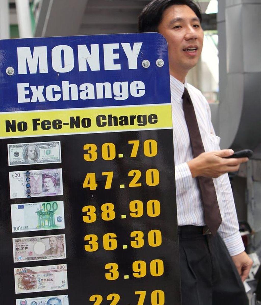 Un hombre camina junto a un tablero con los valores de distintas divisas en el distrito financiero de Bangkok, Tailandia. EFE/Archivo