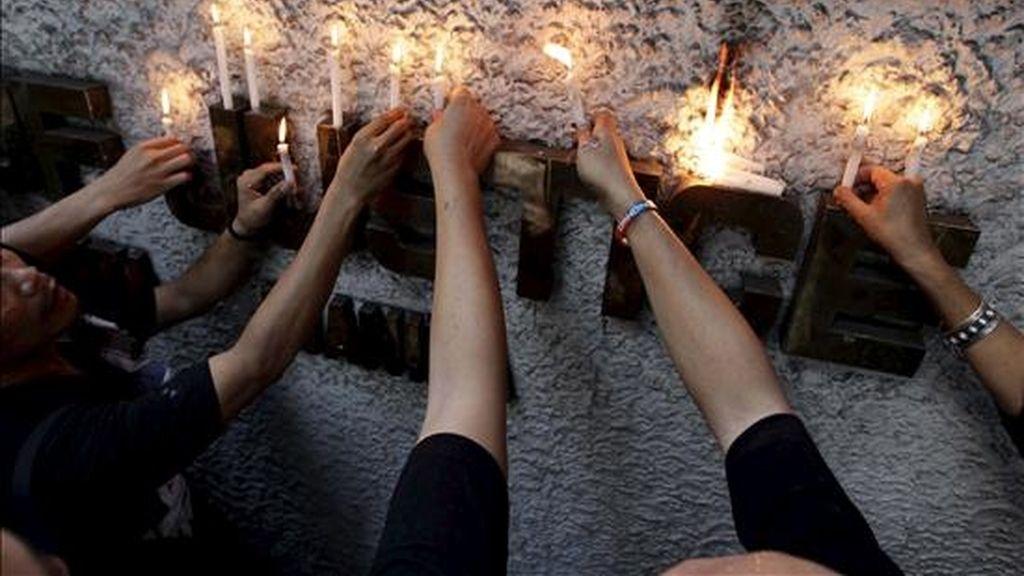 Periodistas filipinos depositan velas durante una manifestación realizada frente al ministerio de Justicia en Manila, Filipinas, hoy, 23 de noviembre de 2010, para pedir justicia por las 57 víctimas mortales de la masacre ocurrida en Maguindanao, cuando los sicarios de un poderoso clan asesinaron a los integrantes del convoy electoral de su rival político. EFE
