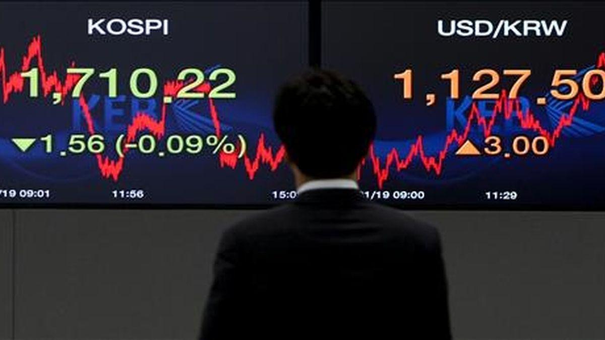 Un agente de bolsa observa dos monitores que muestran la evolución de la Bolsa en el Banco de Cambio de Seúl. EFE/Archivo